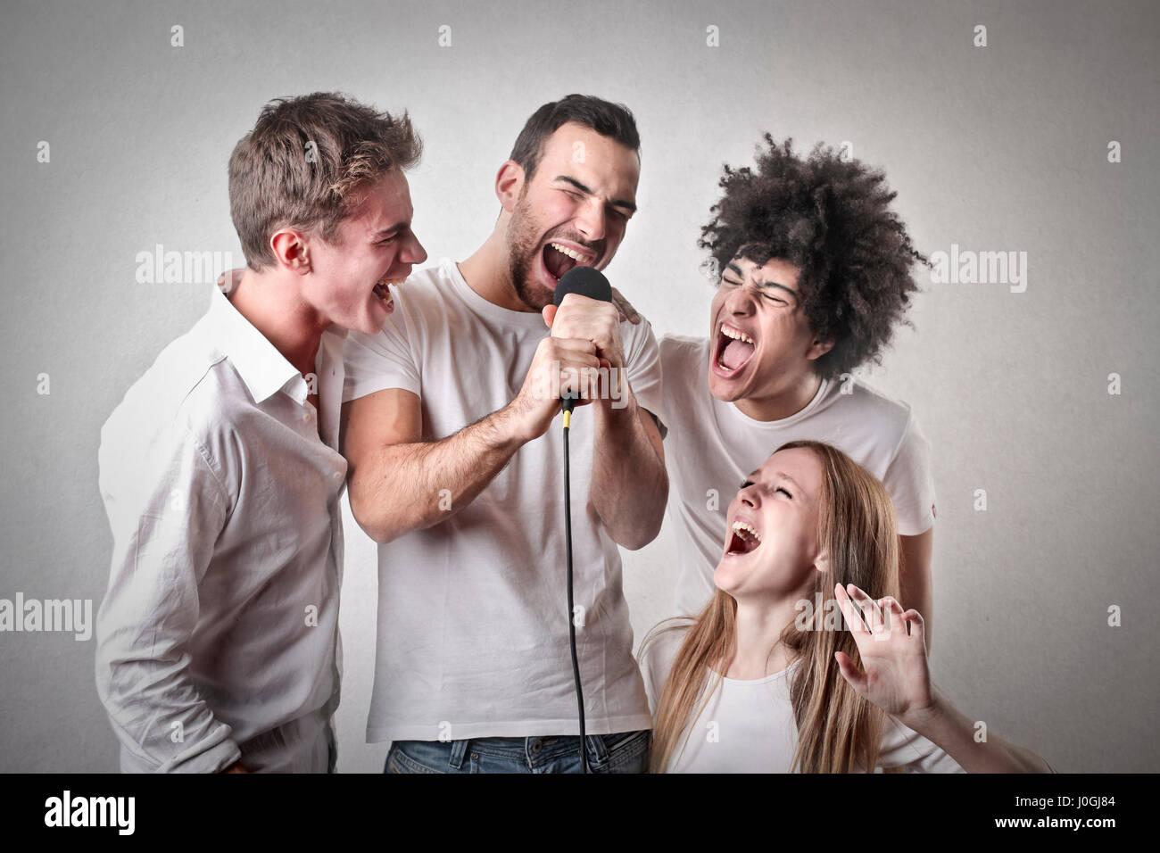 3 hombres y una mujer cantando Imagen De Stock