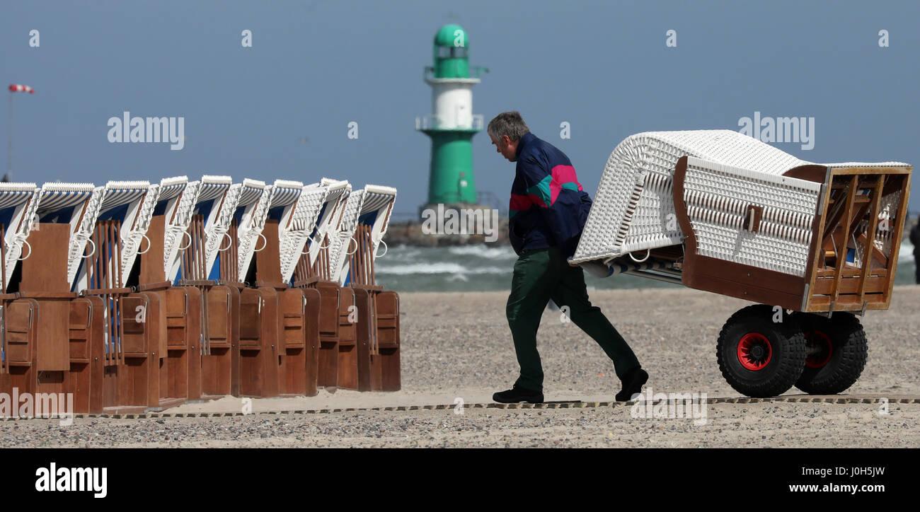 Warnemuende (Alemania). 13 abr, 2017. Un hombre pone alquilables pueden alquilar sillas de playa para el fin de semana de Semana Santa en la ciudad de Mar Báltico Warnemuende (Alemania), 13 de abril de 2017. Según el Servicio Meteorológico Alemán (DWD), el clima seguirá siendo caprichoso y frío en este año de la Semana Santa. Foto: Bernd Wüstneck/dpa-Zentralbild/dpa/Alamy Live News Foto de stock