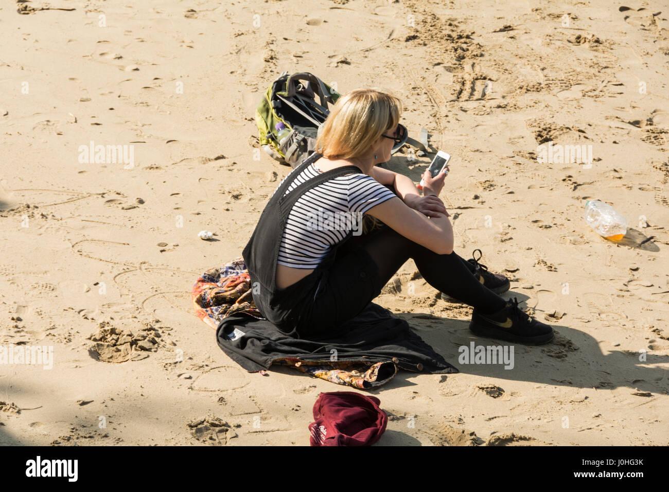 Una solitaria mujer sentada sola en la playa al lado del río Támesis, cerca de South Bank de Londres. Foto de stock