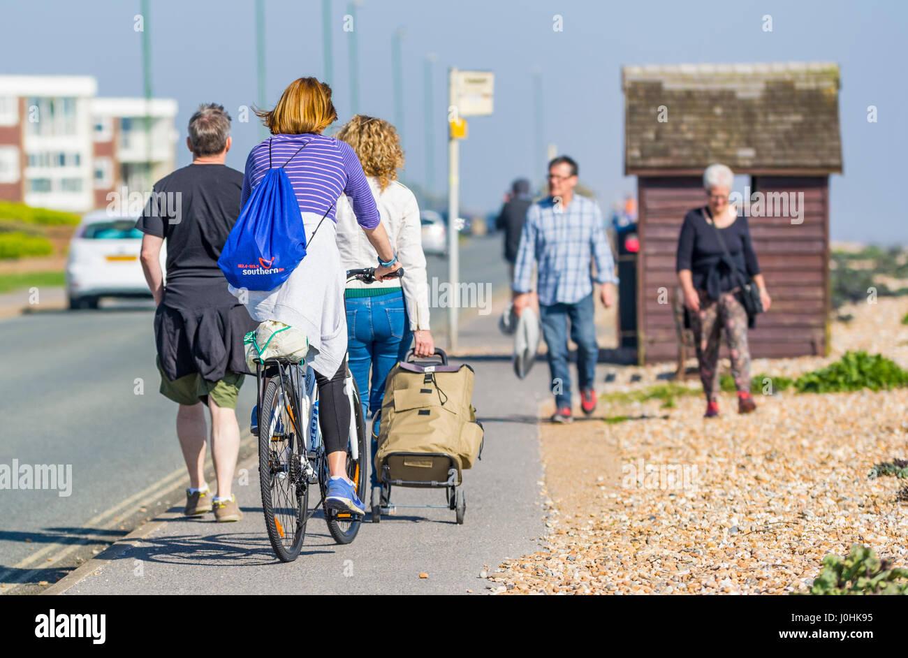 Ciclista en una acera está bloqueado por la gente caminando. Imagen De Stock