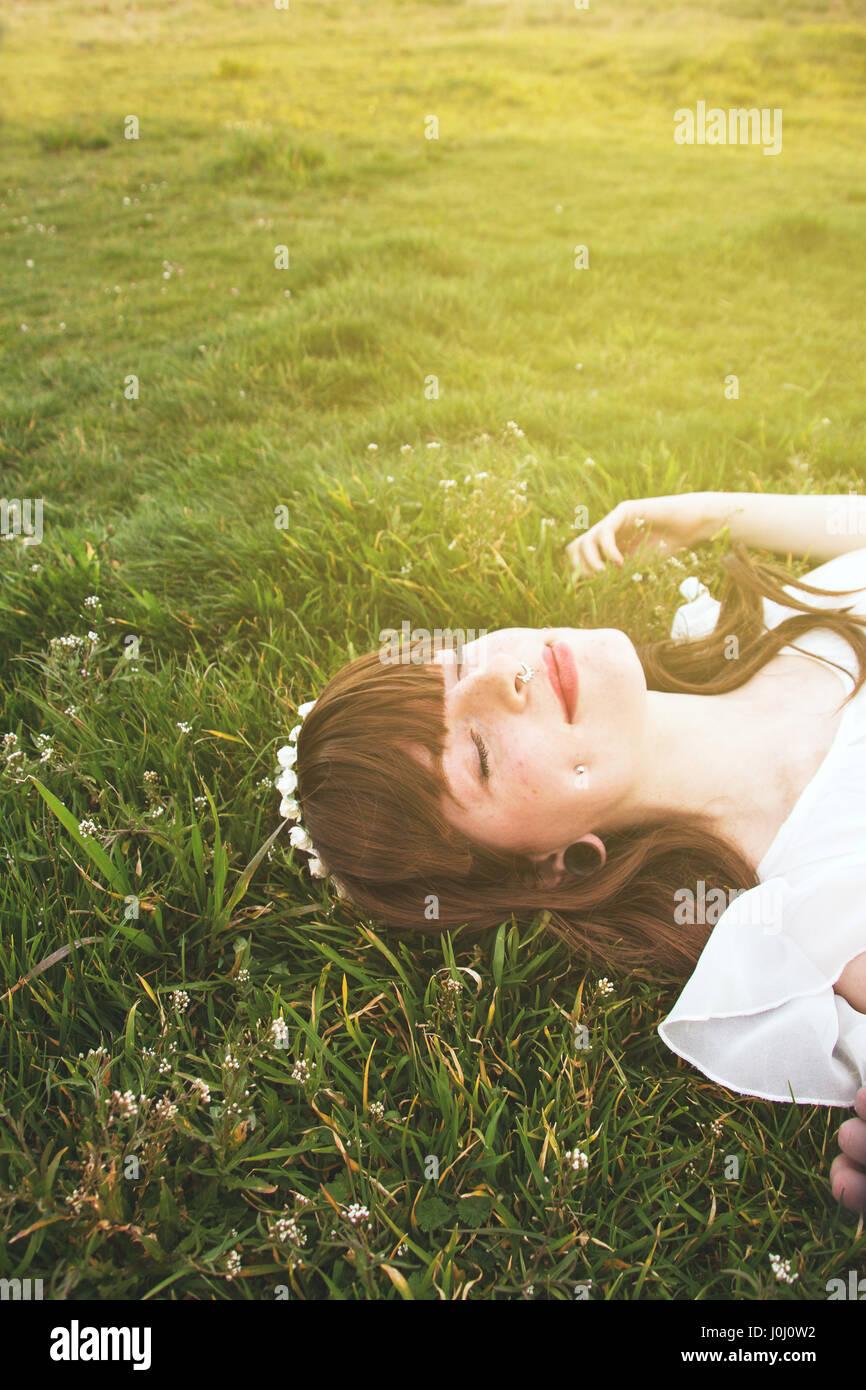 Joven Mujer hippie durmiendo sobre un campo verde Imagen De Stock