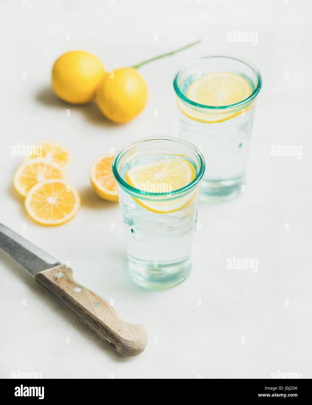 Mañana detox agua de limón en vidrios y limones frescos Foto de stock