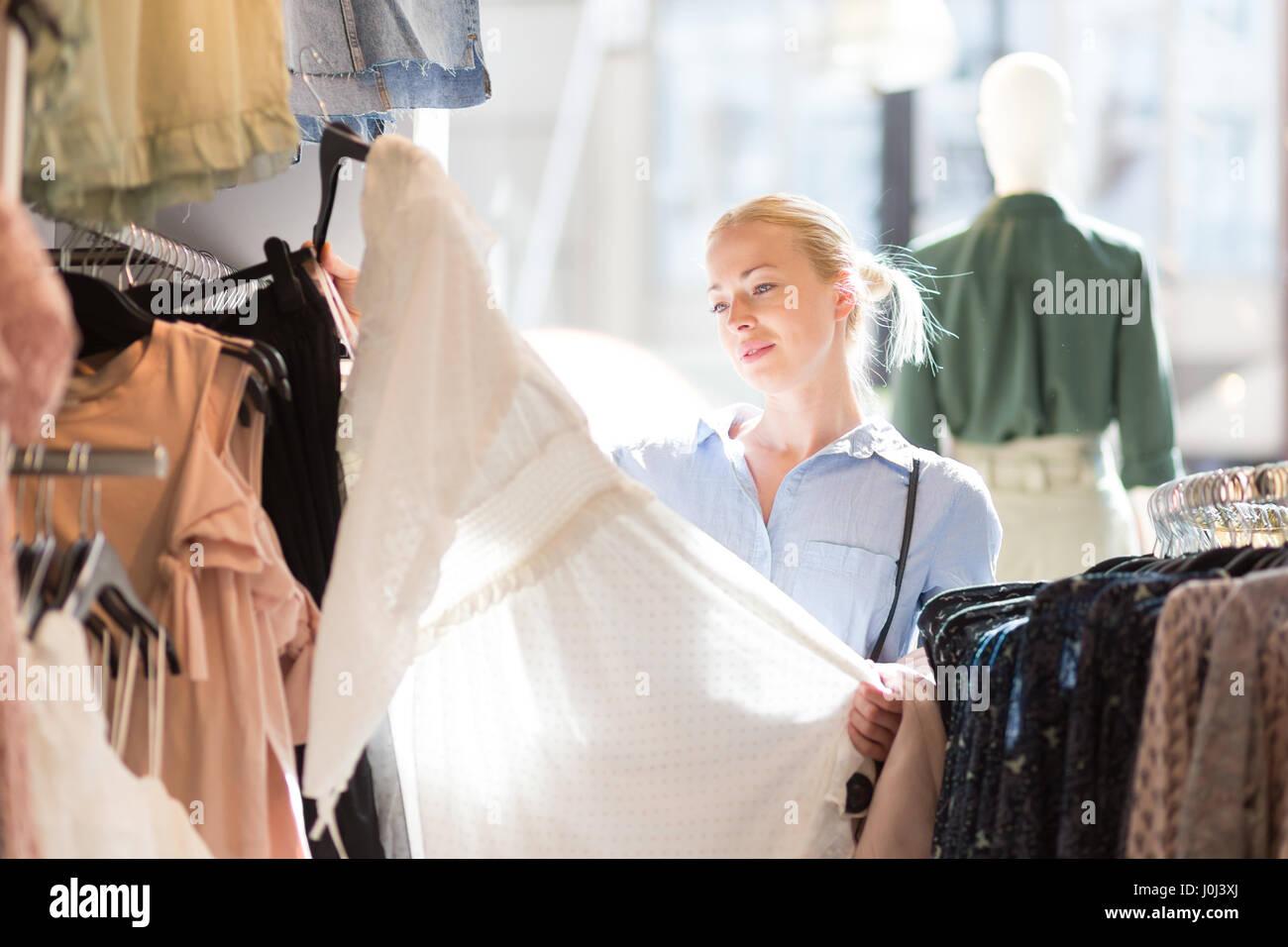 Bella mujer comprar ropa de moda en la tienda de ropa. Foto de stock