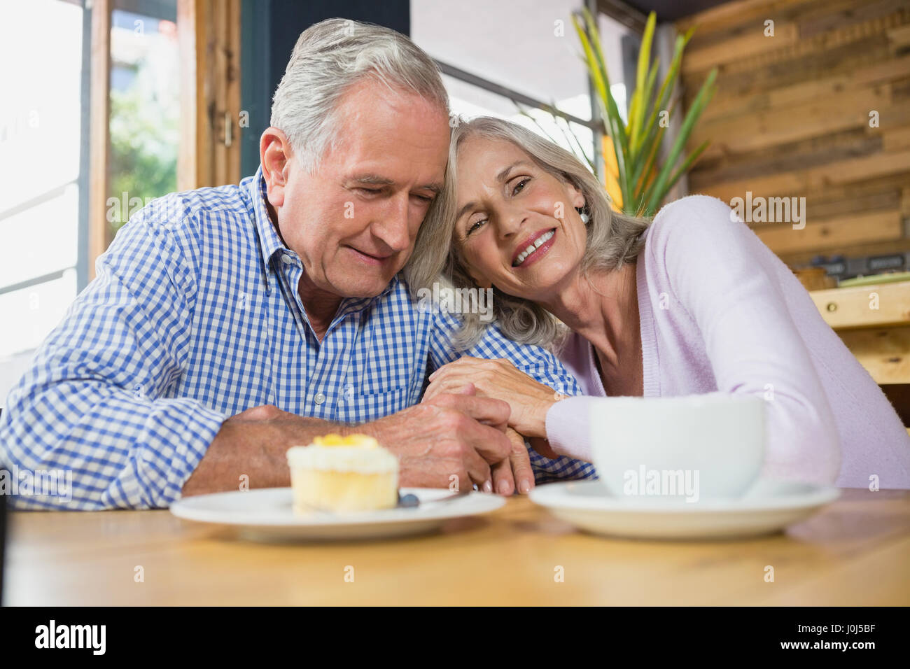 Senior feliz pareja abrazándose entre sí café Foto de stock