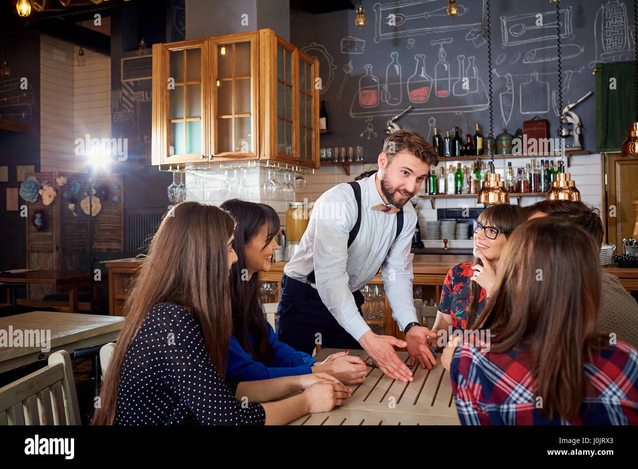 Comunicación de amigos a la mesa en el bar cafetería Imagen De Stock