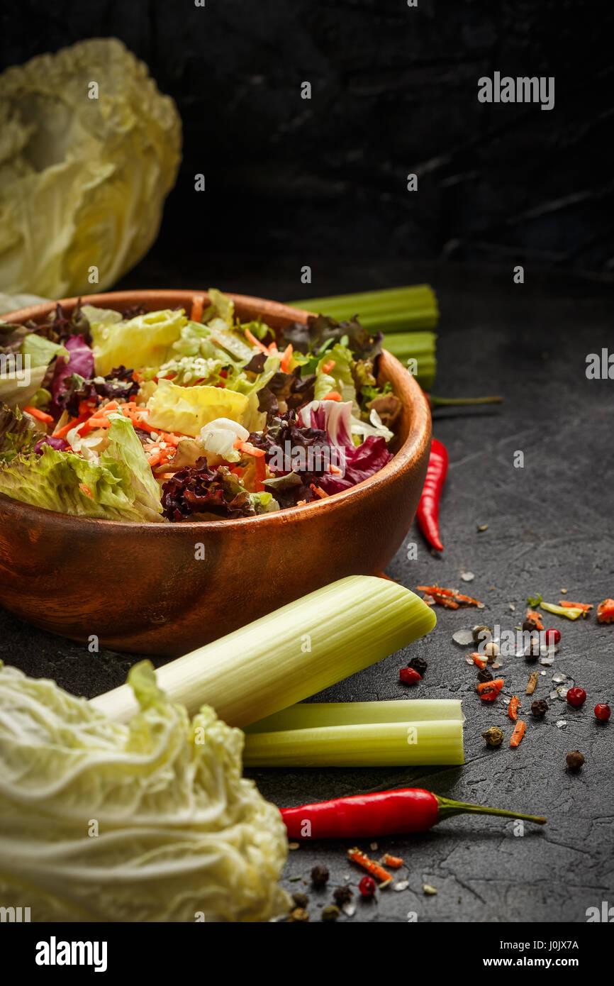 Recipiente de madera con una mezcla de ensalada de congelación, Lollo Rosso, radicchio, romano y el iceberg con zanahorias sobre fondo negro Foto de stock