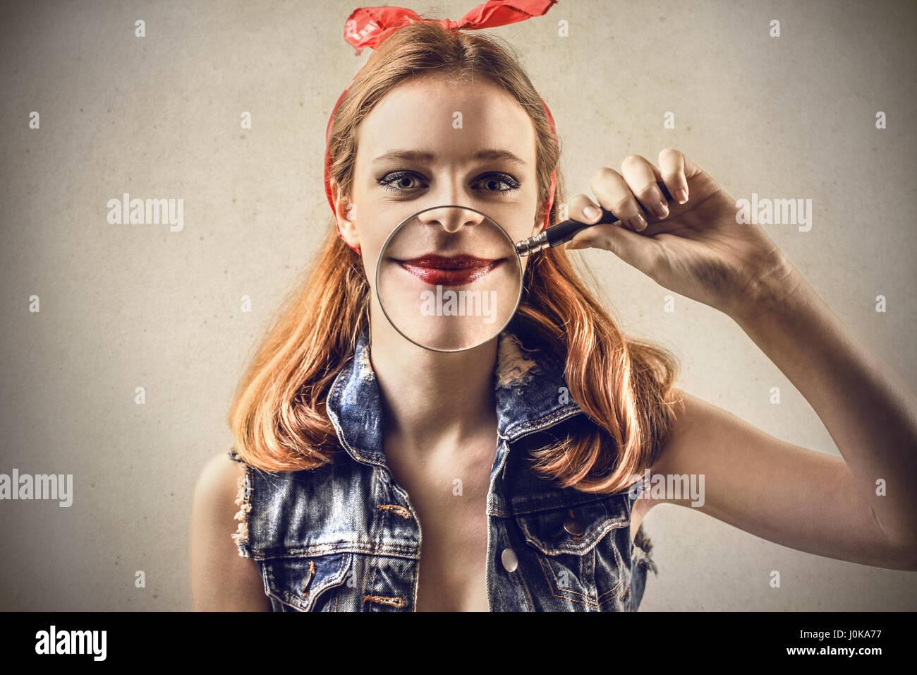Mujer rubia poniendo la lupa a la boca Foto de stock