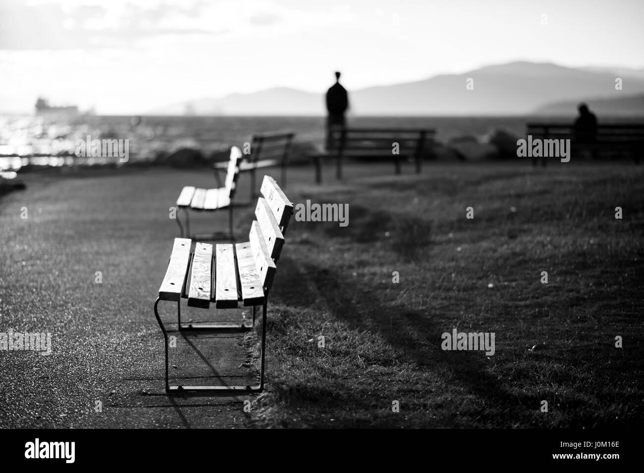 Uno blurrred silueteado hombre parado mirando hacia el océano, otro sobre un banco. Imagen De Stock