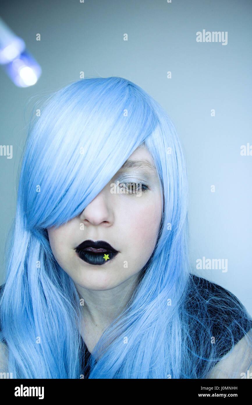 Mujer joven con cabello azul y maquillaje creativo Imagen De Stock