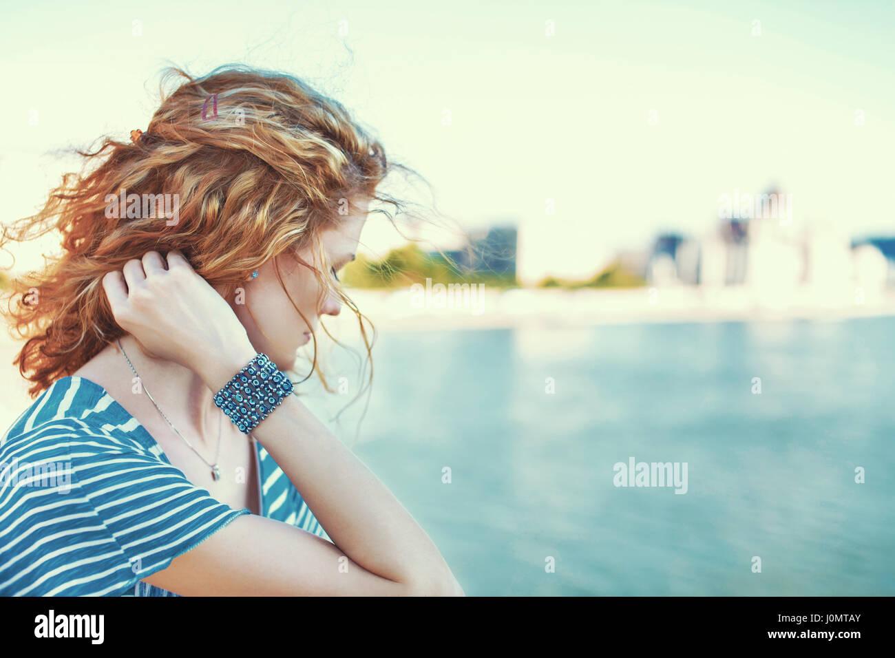 Triste pelirroja mujer mirando lejos sobre el río piscina Imagen De Stock