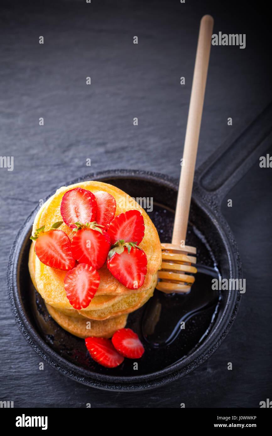 Pila de panqueques con dulce de fresa y miel. Imagen De Stock
