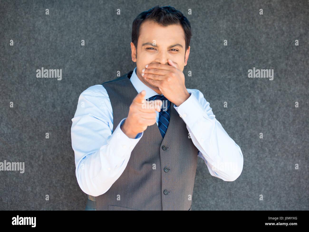 Closeup retrato de guapo excitado, gerente boss man en chaleco y corbata, feliz sonrisa, apuntando hacia los dedos en el gesto de cámara, aislada gr Foto de stock