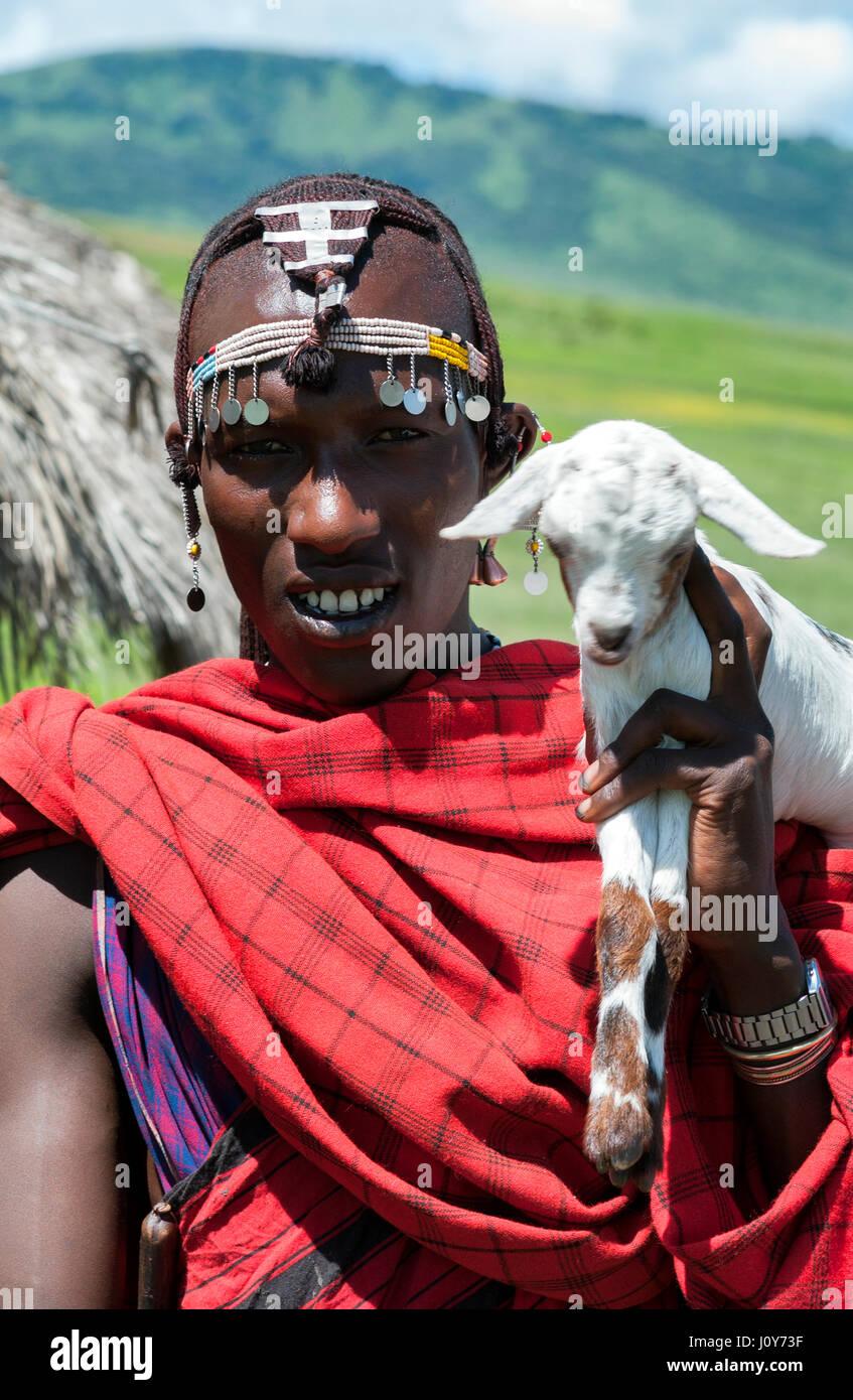 Retrato de un joven guerrero maasai tanzaniano de África oriental en cuentas de joyería tribal y ornamentos de plata, tradicional túnica roja Shuka y Gato Blanco. Foto de stock