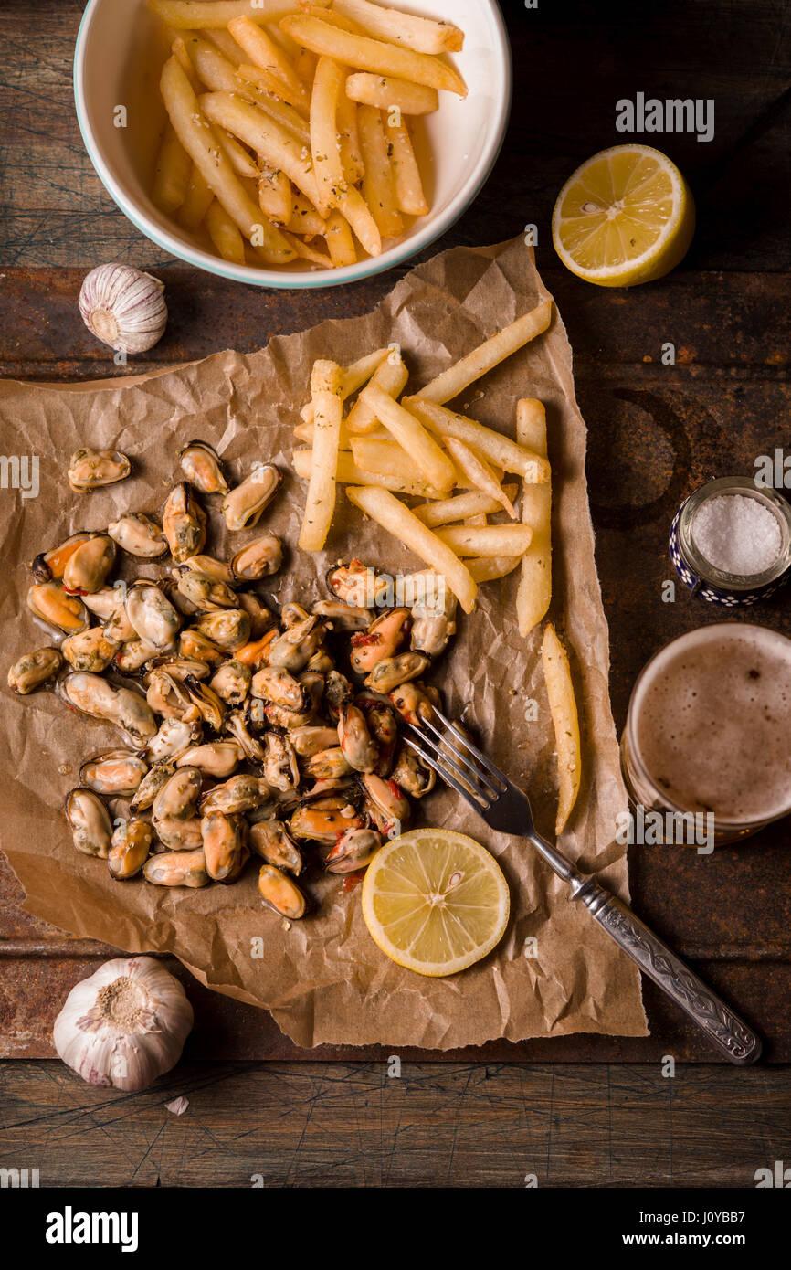 Los limones y mejillones con patatas fritas en el fondo de metal verticales Imagen De Stock