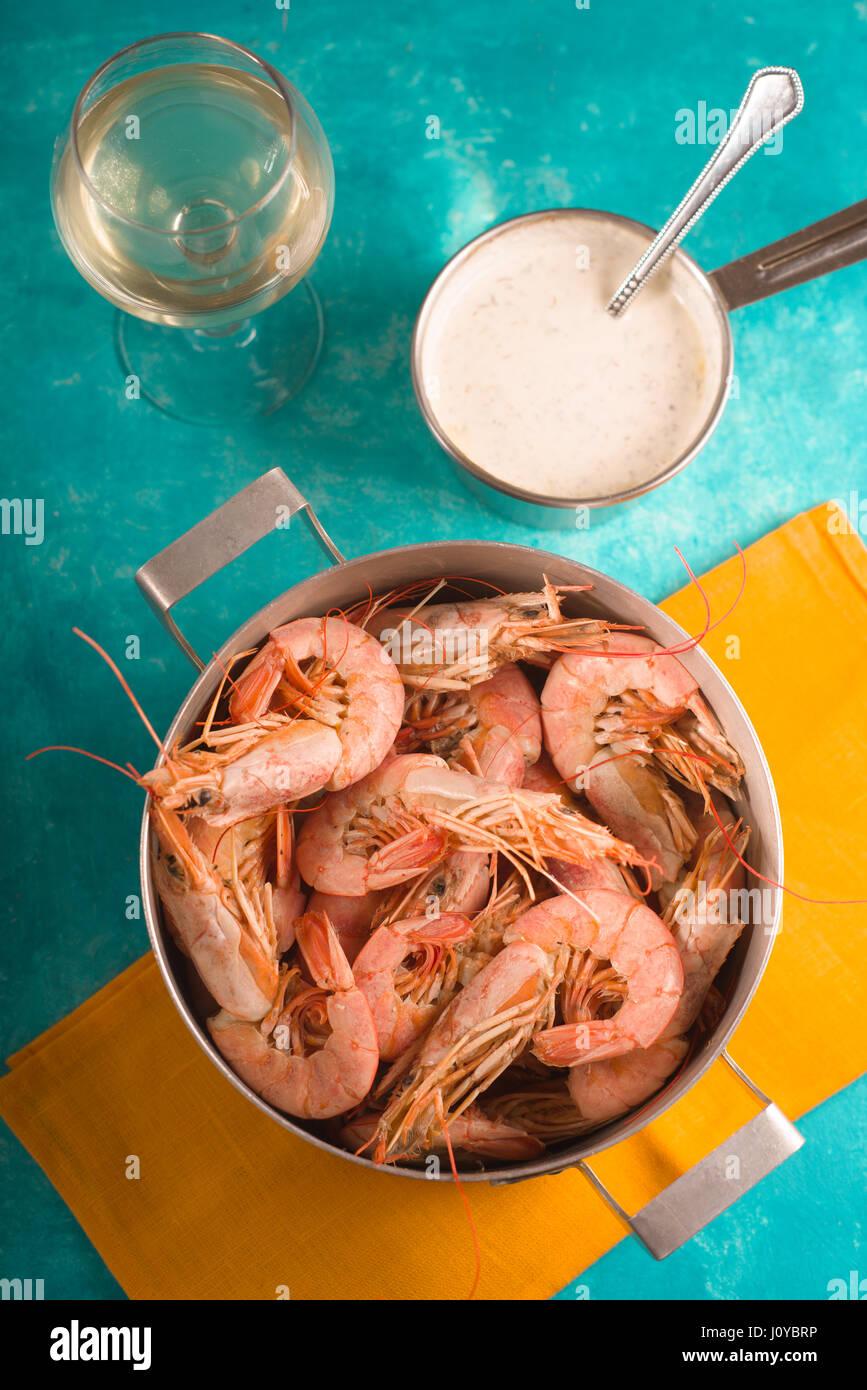 Camarones en una servilleta amarilla, cristal con vino blanco y salsa Foto de stock