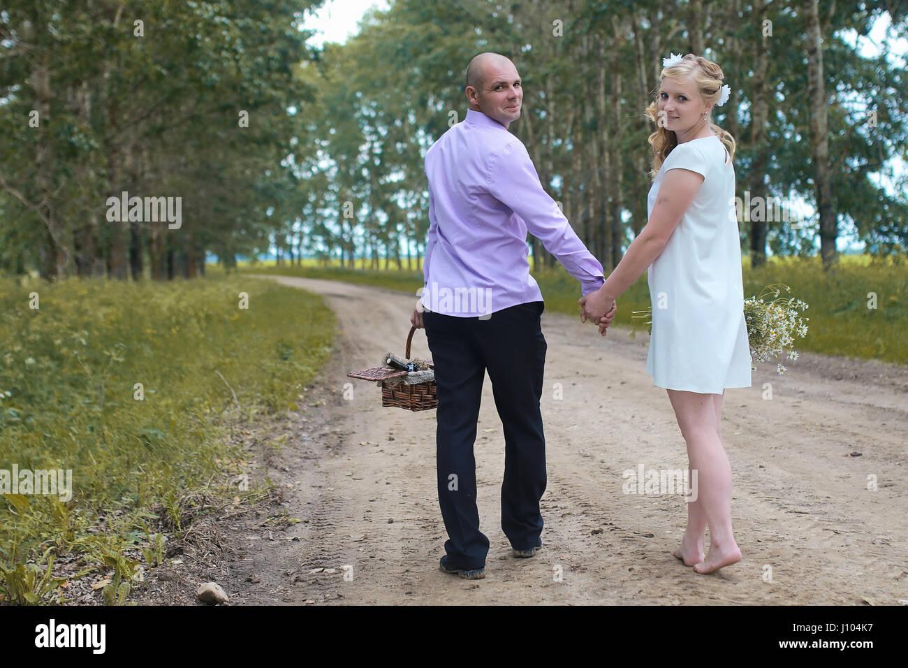 Los amantes recién casados caminando en un campo en el día de otoño Imagen De Stock