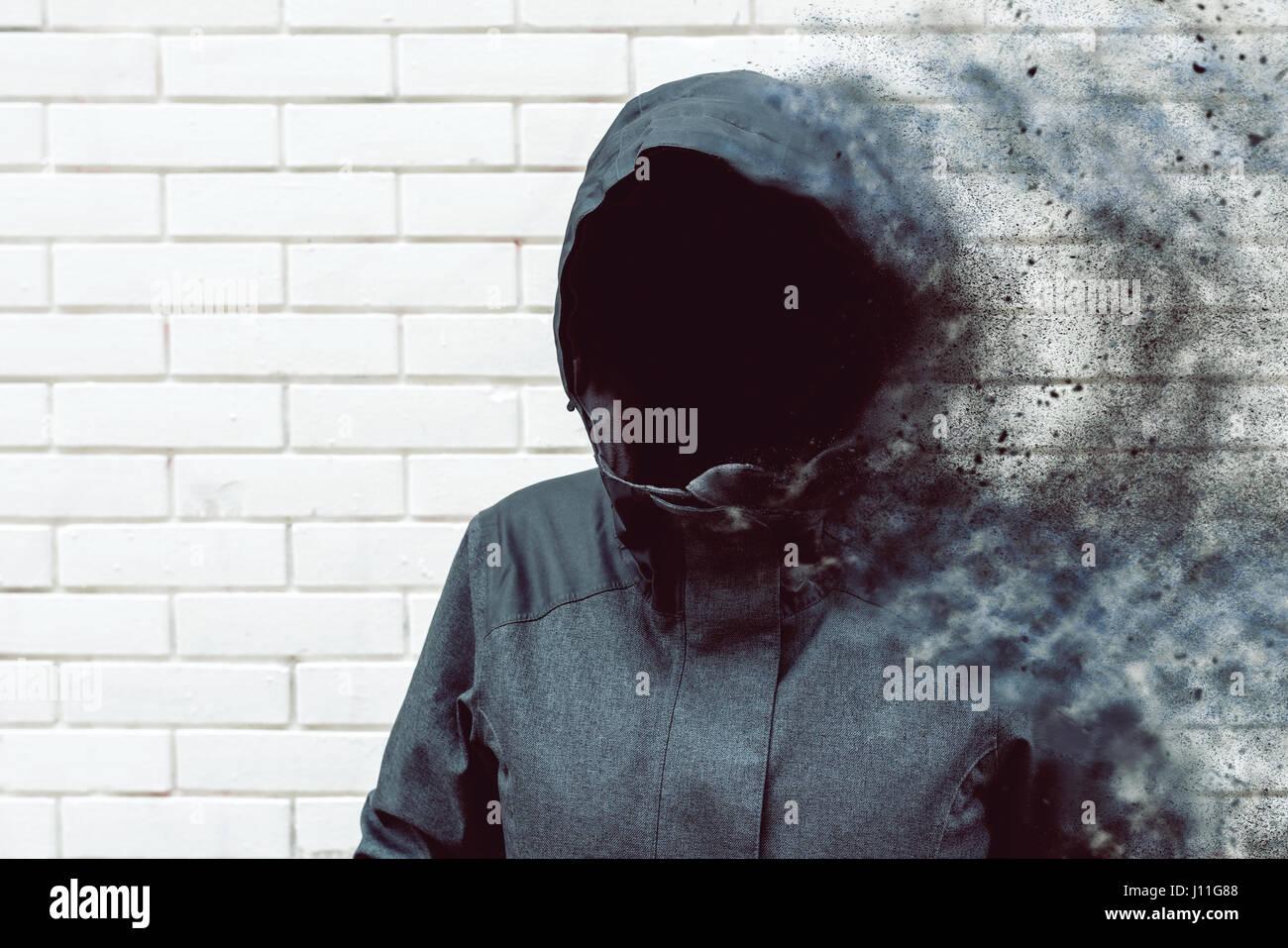 Pensando soplar de la mente pensamientos, sin rostro encapuchado persona contra la pared de ladrillo blanco. Imagen De Stock