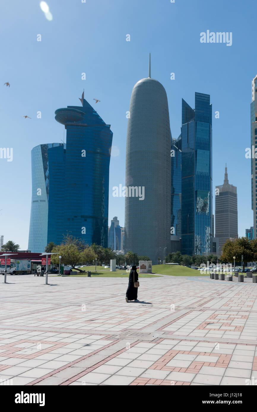 Ciudad de Doha, Qatar, en Oriente Medio, una mujer andando desde la cámara usando un Shayla sobre su cabeza Imagen De Stock