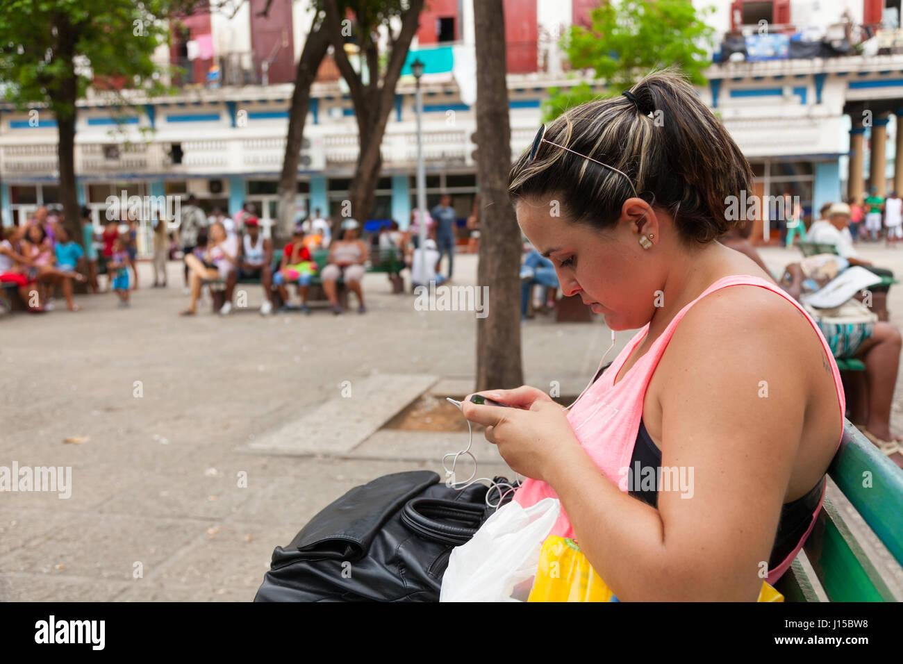 Una mujer cubana utilizando su smartphone en un hotspot wifi pública en La Habana, Cuba. Imagen De Stock