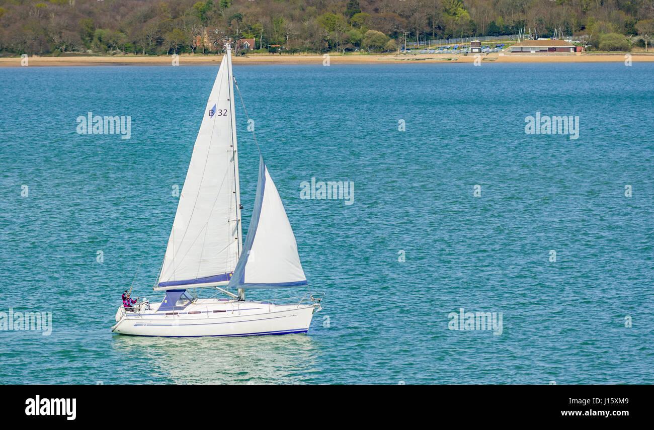 Pequeño yate blanco. Pequeño yate con velas hasta la vela en un estrecho tramo de agua cerca del mar, Imagen De Stock