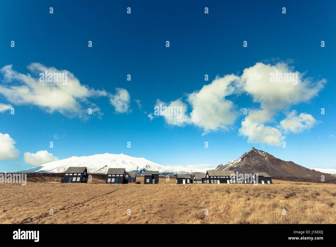 Negro Casas en un campo dorado, Hellnar, península de Snaefellsnes, en el oeste de Islandia Foto de stock
