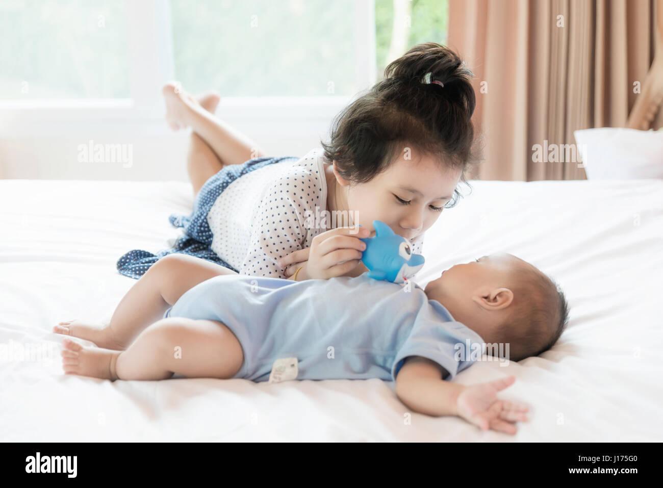 Bebé asiático hermano y hermana niño jugando peces doll en el dormitorio. Familia Feliz. Imagen De Stock