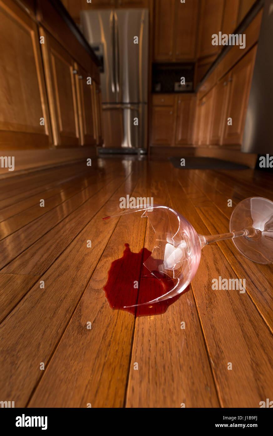Copa de vino rota en el piso de la cocina moderna - concepto de violencia doméstica Imagen De Stock
