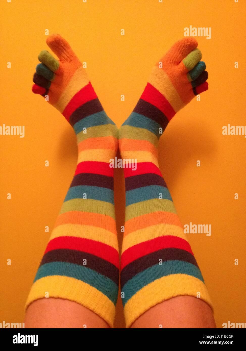 Stripey toe socks. poner los pies en la pared en cómodos calcetines toe Imagen De Stock
