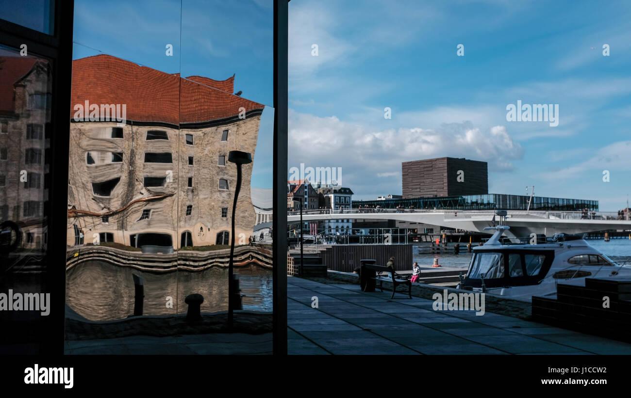 Reflexión distorsionada del viejo edificio en el restaurante noma de nuevo desarrollo con Inderhavnen Krøyers Plads puente y Royal Danish Playhouse en segundo plano. Foto de stock