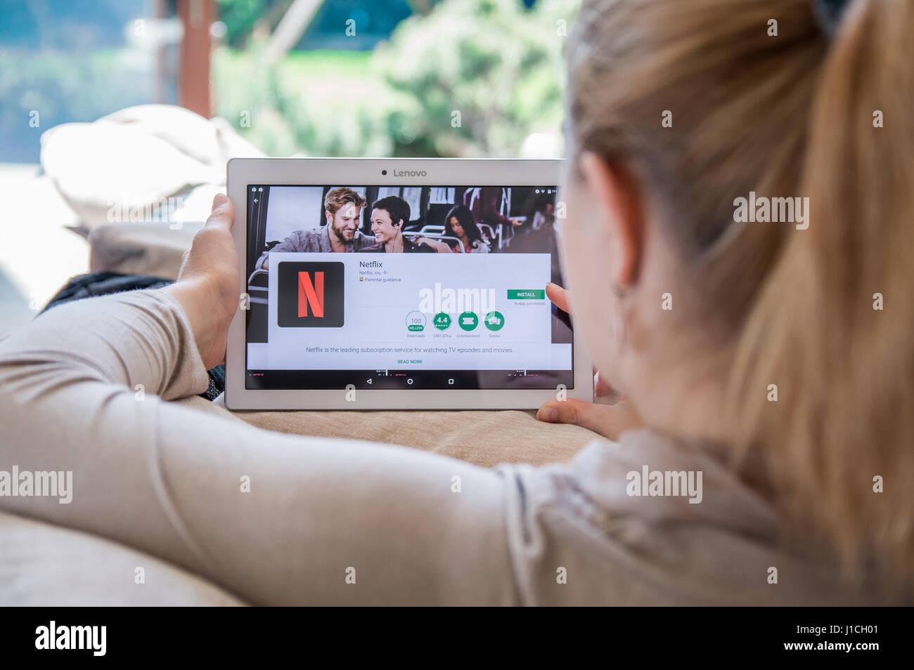 WROCLAW, Polonia- Abril 10th, 2017: la mujer es instalar la aplicación Netflix en Lenovo tablet. Netflix es Imagen De Stock