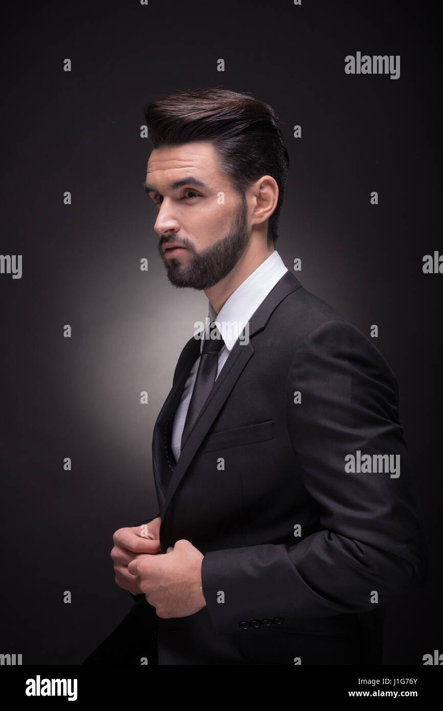 Un joven apuesto hombre abotonadura unbuttoning traje chaqueta perfil c423b0df686