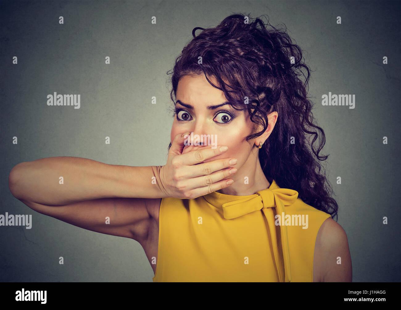 Closeup retrato de mujer joven asustado con la mano cubriendo su boca aislado sobre fondo de pared gris Imagen De Stock