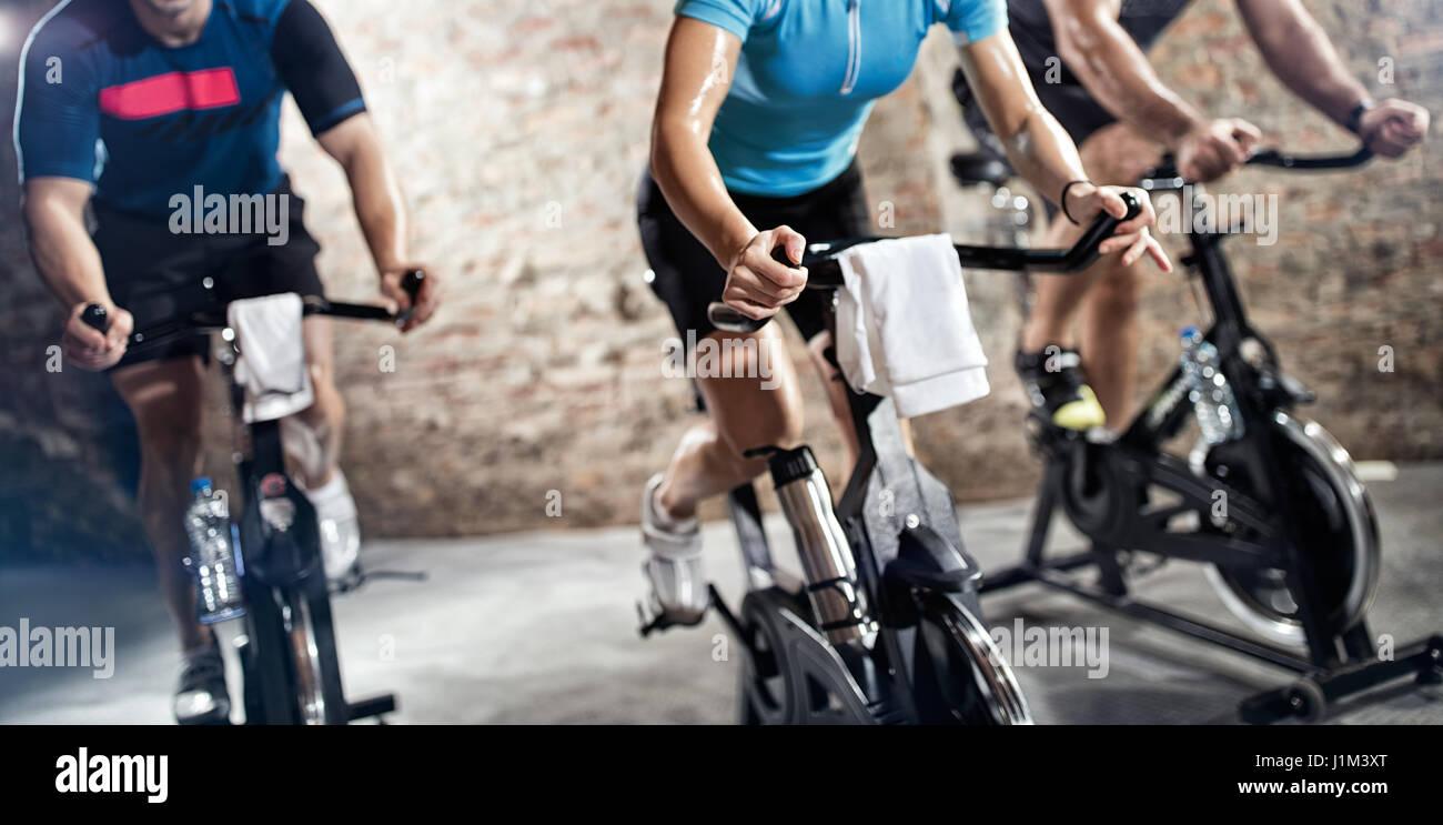 La gente de ropa de deporte de equitación, bicicletas de ejercicio cardio fitness class Imagen De Stock