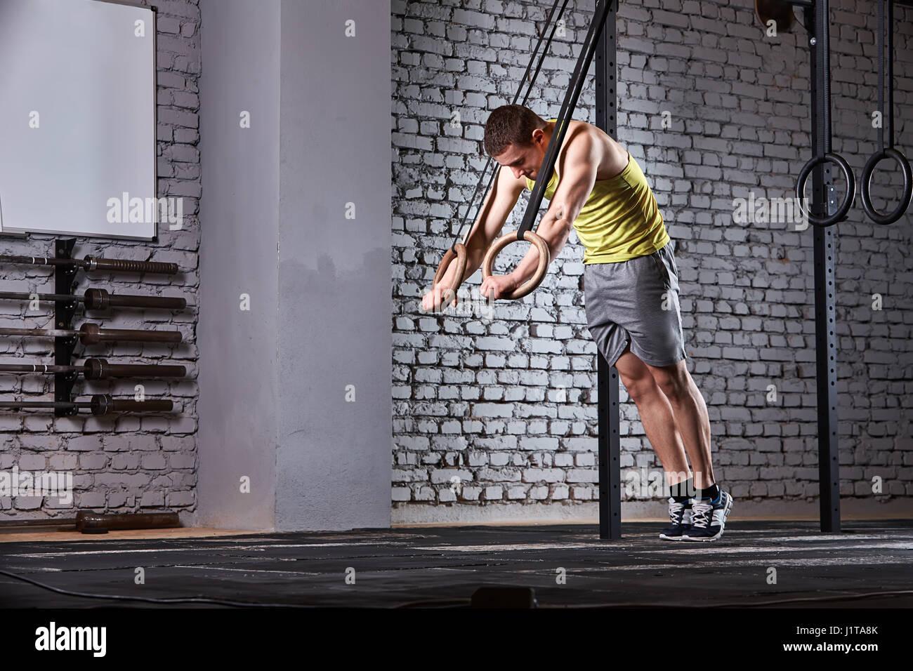 Atlético joven hombre en el sportwear entrenamiento en el gimnasio con anillos de cross fit contra la pared de ladrillo. Foto de stock