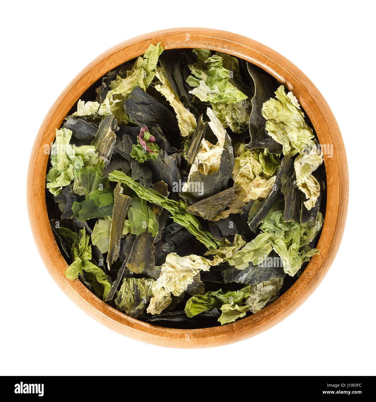 Las algas secas escamas en el tazón de madera. Mezcla de lechuga de mar, wakame y nori. Las Algas verdes comestibles y algas. Ulva lactuca, Undaria pinnatifida. Foto de stock