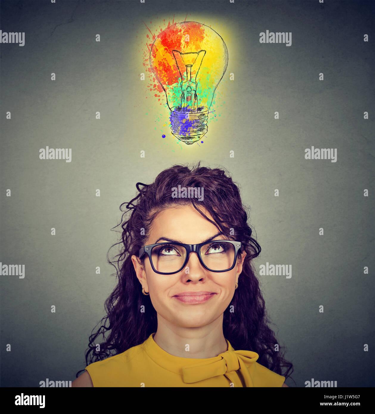 Retrato de una mujer con gafas y creativa idea mirando hacia la luz colorida lámpara en pared gris de fondo. Imagen De Stock