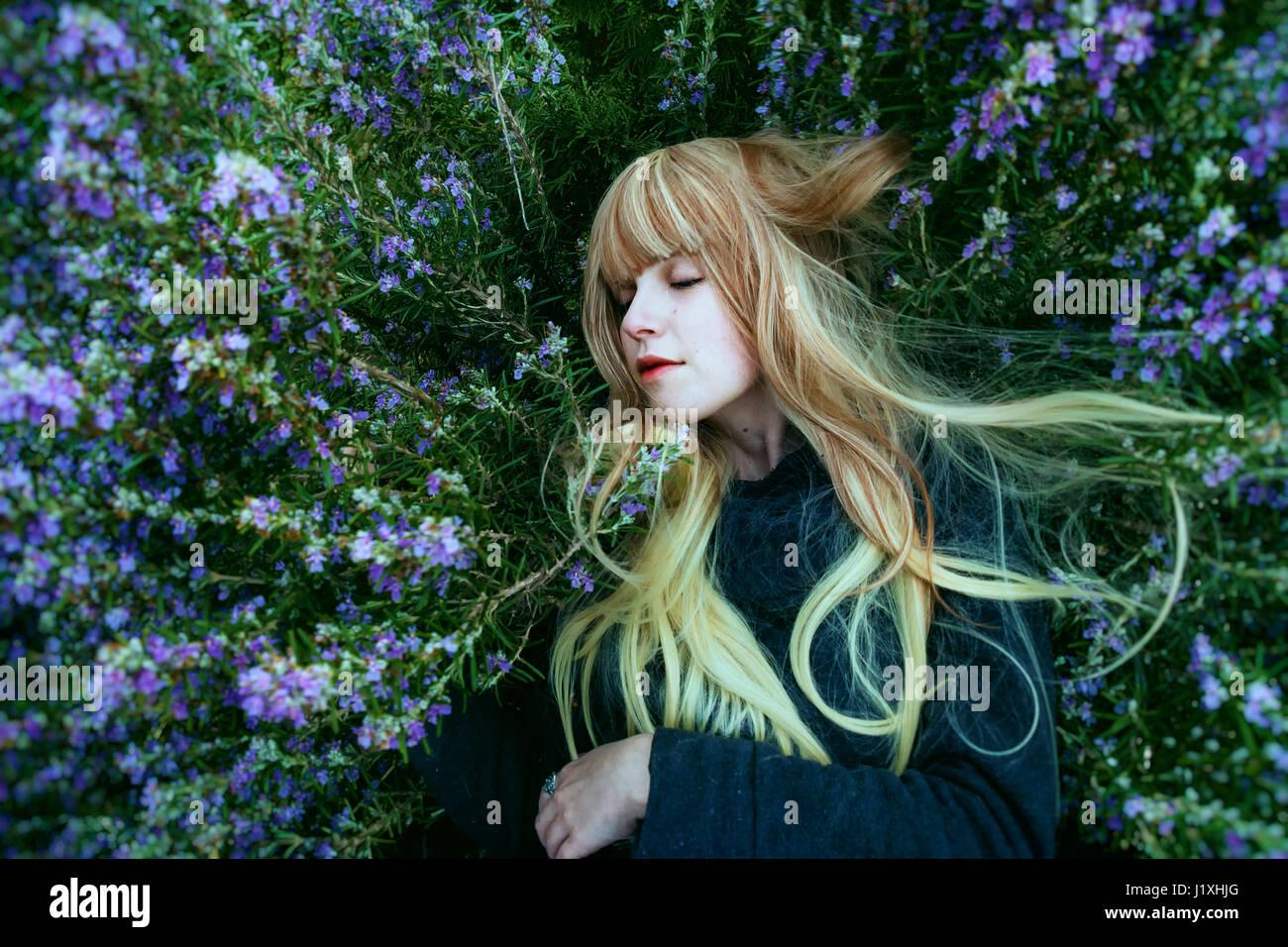 Mujer joven acostado en un arbusto de romero Imagen De Stock