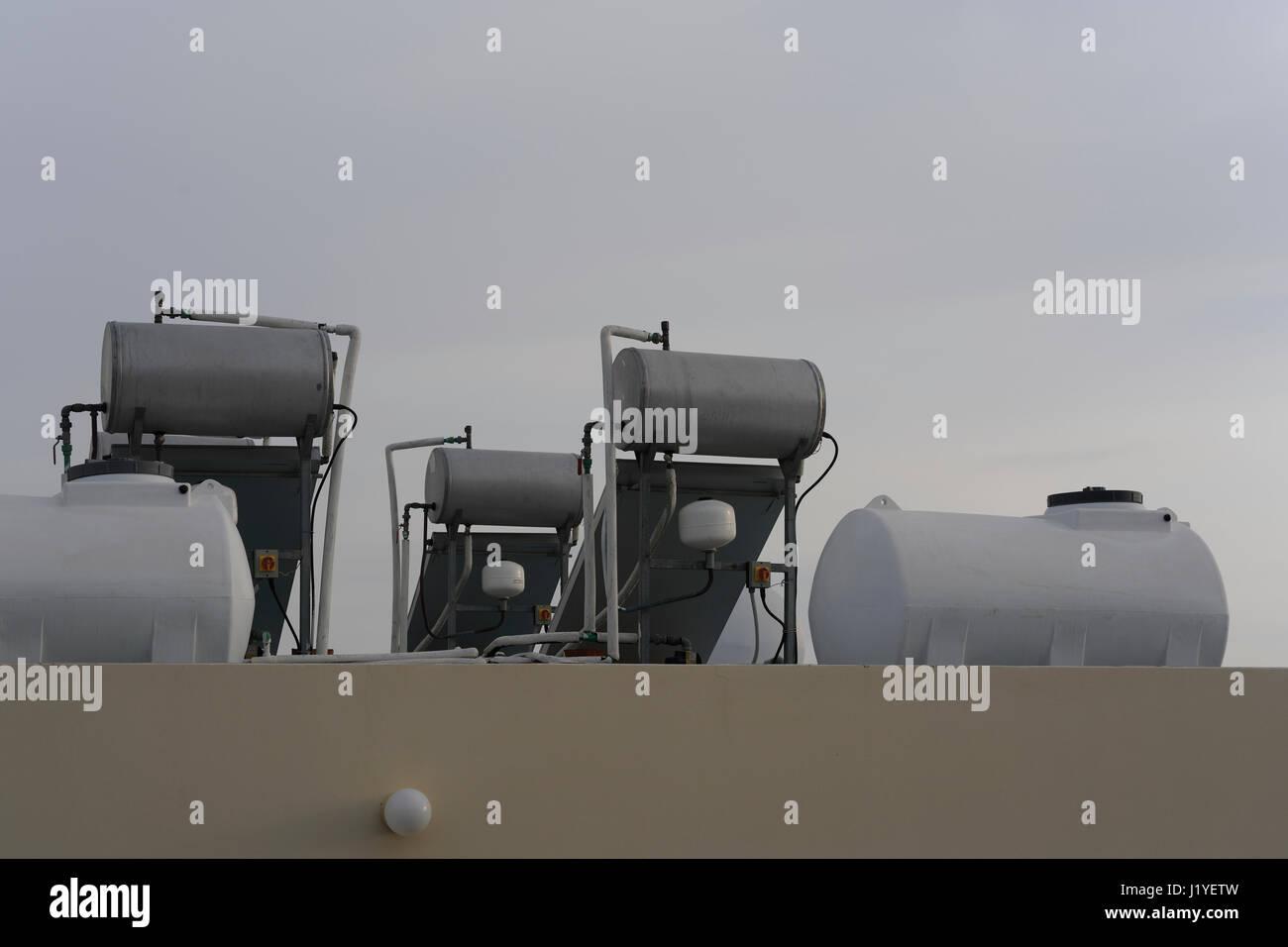 Techo montado en unidades de calentamiento de agua por energía solar en Chipre contra un cielo gris Imagen De Stock