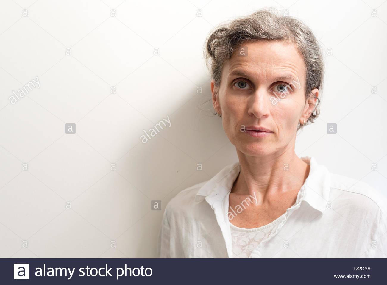 Cabeza y hombros vista de mujer de mediana edad con cabello gris aspecto cansado (enfoque selectivo) Imagen De Stock