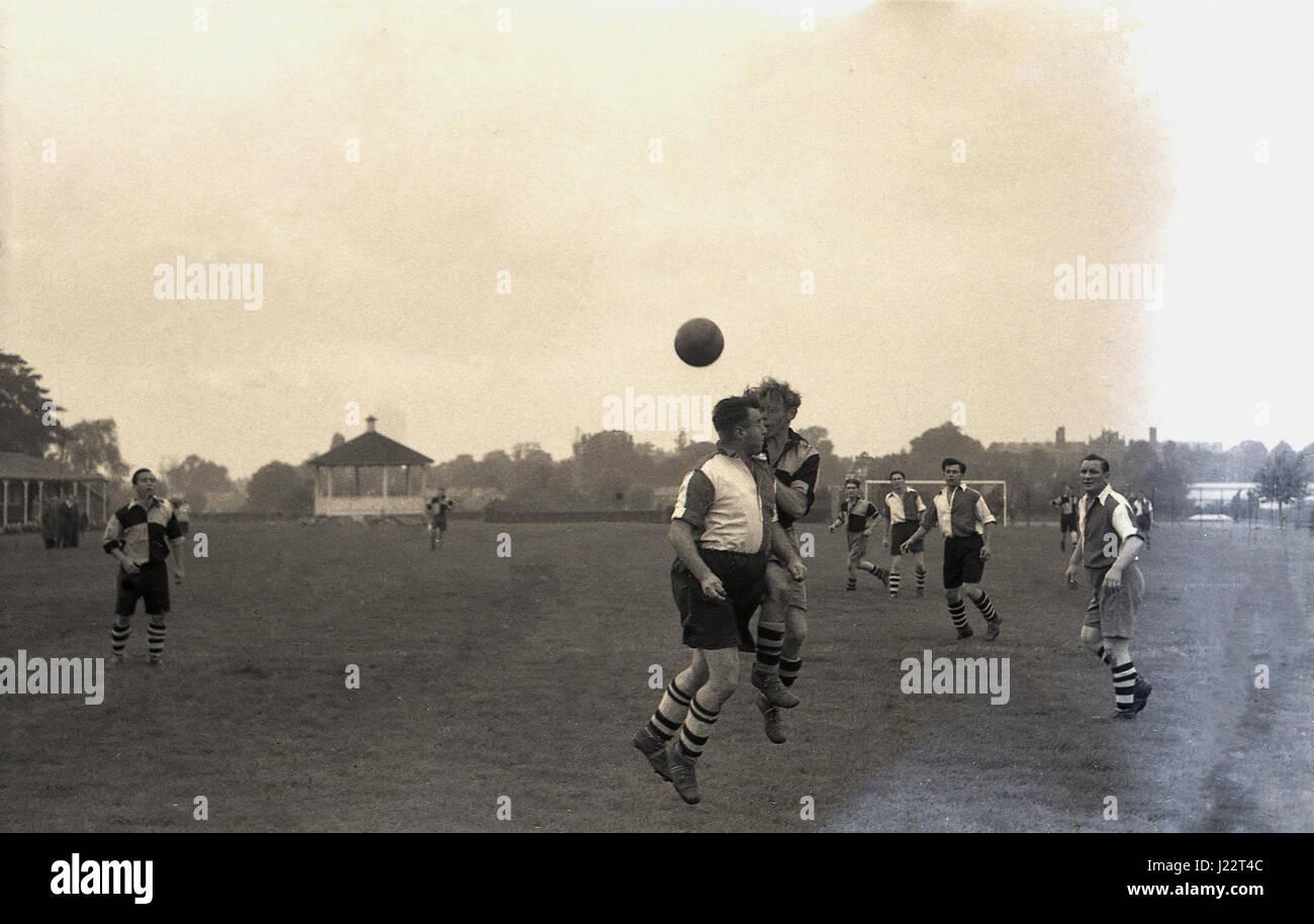 1950, un partido de fútbol amateur, dos futbolistas en largas y pantalones holgados tobillo botas de cuero altas compiten por el balón en el aire, Inglaterra. En el Reino Unido. Foto de stock