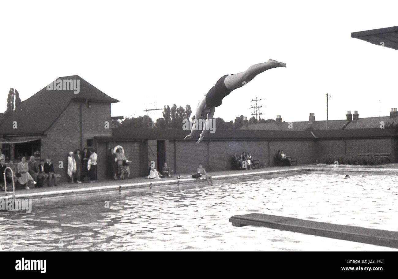 1950, hembra buceo desde una plataforma o trampolín en una piscina al aire libre, Inglaterra, Reino Unido. Foto de stock