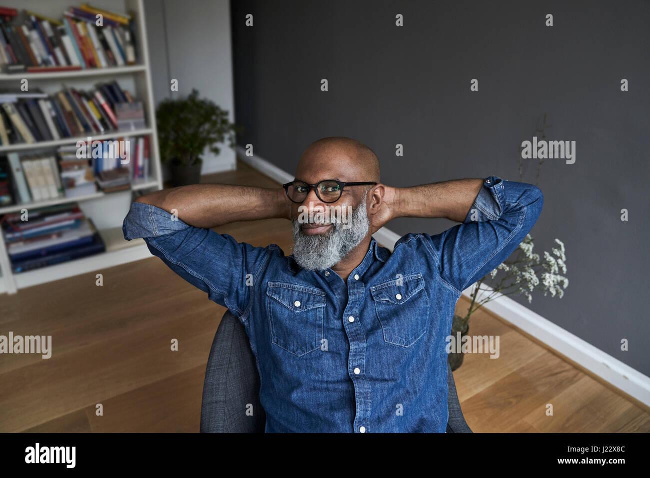 Hombre maduro sentado relajado en casa Imagen De Stock