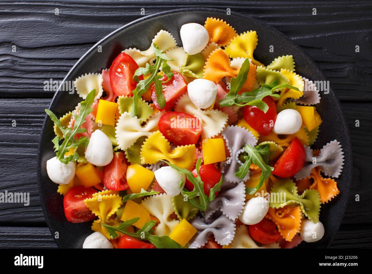 Comida italiana: Pasta Farfalle con verduras y mozzarella de cerca en una placa vista desde arriba de la horizontal. Foto de stock