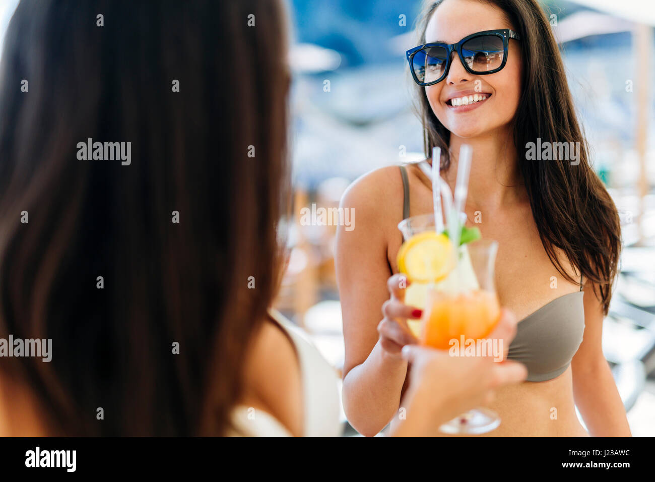 Alegre amigas bebiendo cócteles en verano y sonriente Imagen De Stock