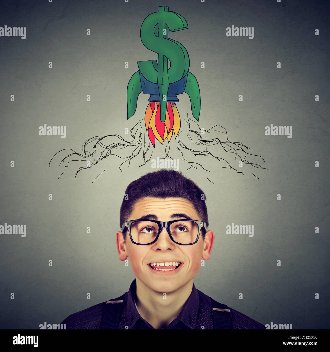 Concepto de éxito de negocio financiero. Feliz joven en copas mirando rocket signo de dólar sobre la cabeza Imagen De Stock