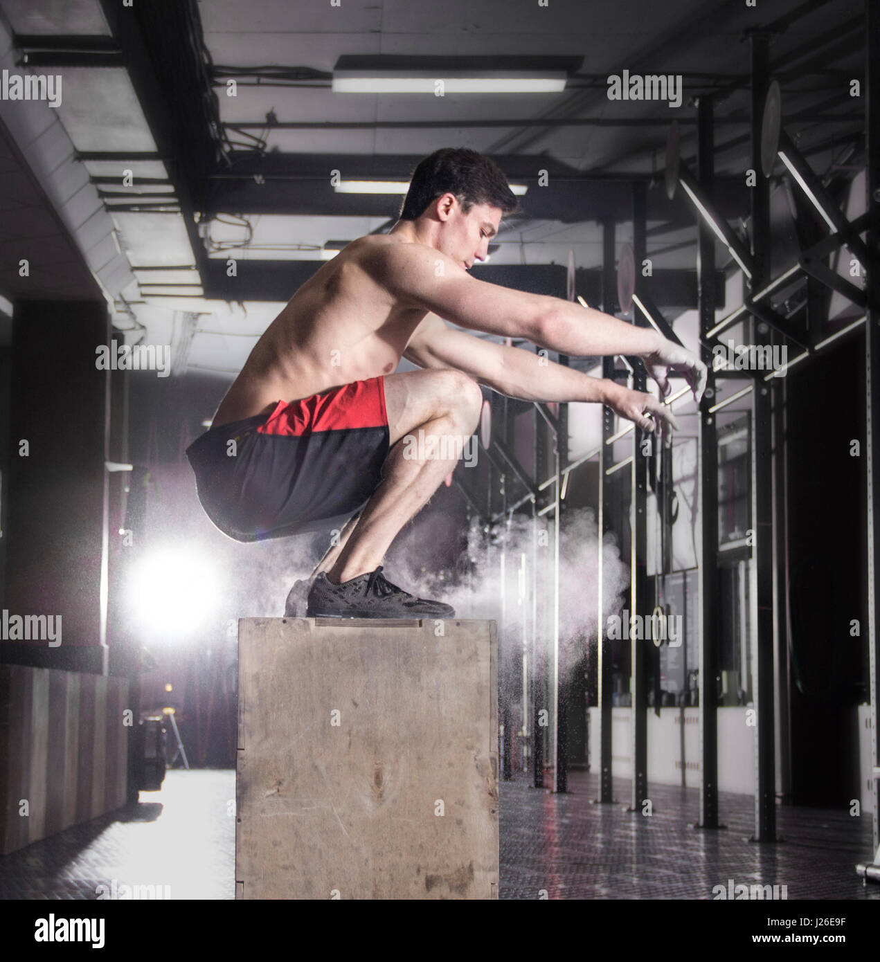 Colocar cuadro joven saltando en un gimnasio crossfit.atleta es performin Foto de stock