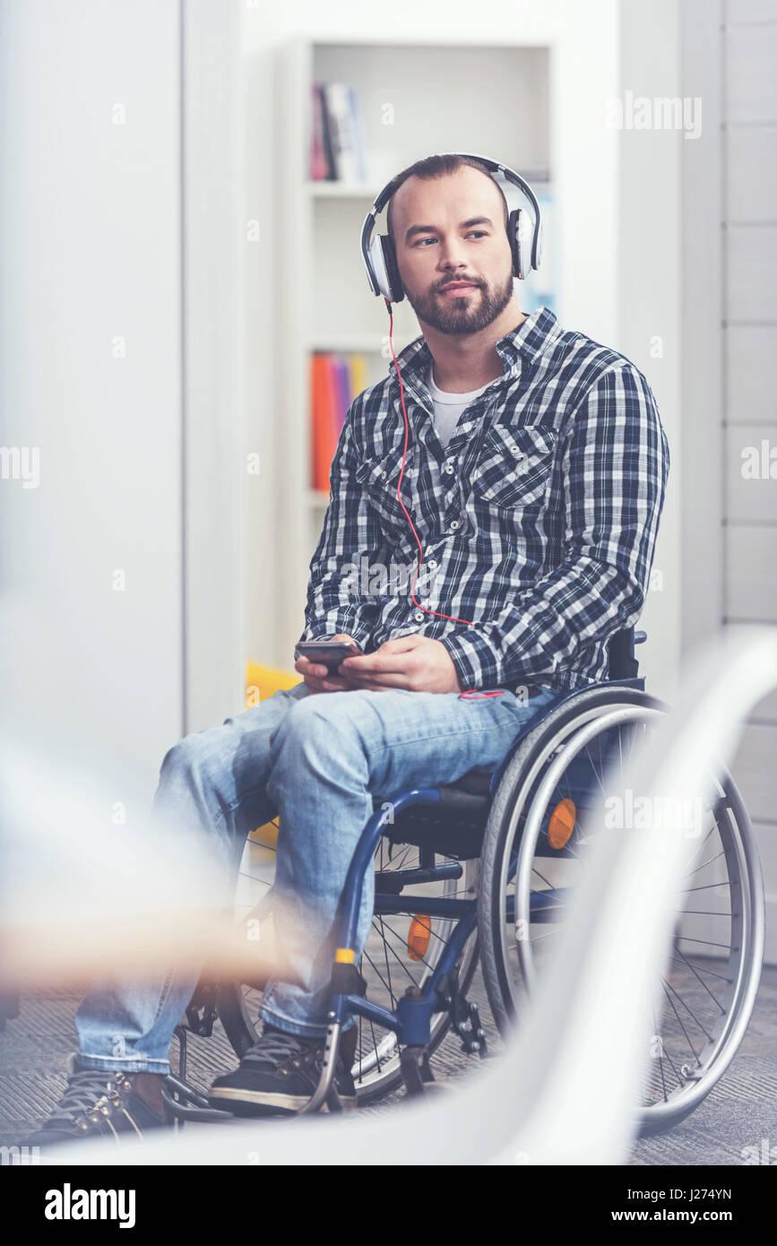 Pasando cada día con música. Participan apuesto hombre barbado sentado en la silla de ruedas en el estudio Imagen De Stock