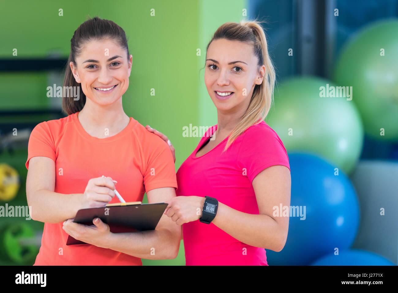 Dos joven disfrutando de su rutina de ejercicios en el gimnasio reír y sonreír Imagen De Stock