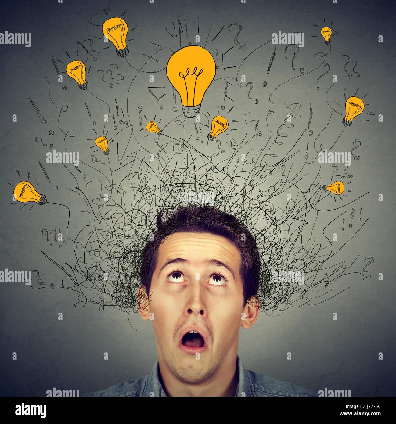 Sorprendido el hombre con bombillas de luz muchas ideas sobre la cabeza mirando hacia arriba aislado sobre la pared Imagen De Stock