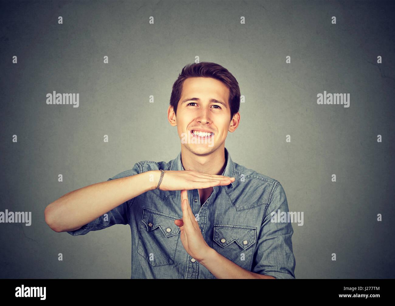 Hombre feliz dando tiempo mano gesto aislado sobre fondo de pared gris Imagen De Stock